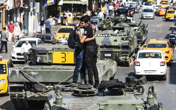 TOPSHOT - Turkish police officer (R) embrace a man on a tank after the military position was taken over at the Anatolian side at Uskudar in Istanbul on July 16, 2016. President Recep Tayyip Erdogan urged Turks to remain on the streets on July 16, 2016, as his forces regained control after a spectacular coup bid by discontented soldiers that claimed more than 250 lives. Describing the attempted coup as a